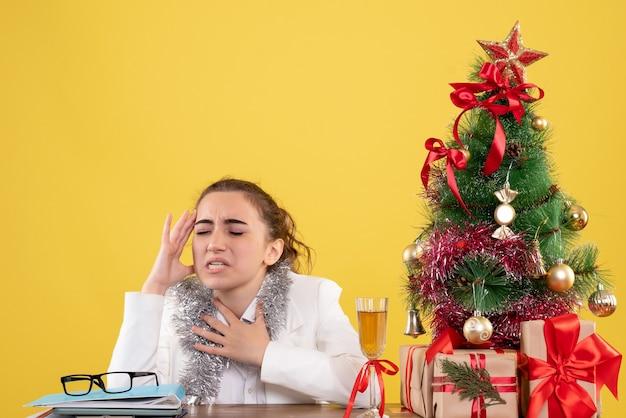Medico femminile vista frontale seduto dietro il suo tavolo con mal di testa su sfondo giallo con albero di natale e scatole regalo