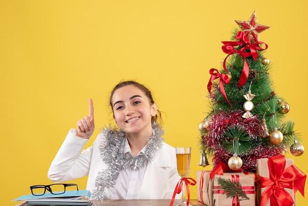 Medico femminile vista frontale seduto dietro il suo tavolo sorridente su sfondo giallo con albero di natale e scatole regalo