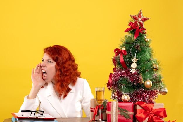 Medico femminile di vista frontale che si siede dietro la sua tavola con i regali di natale e la chiamata dell'albero su fondo giallo