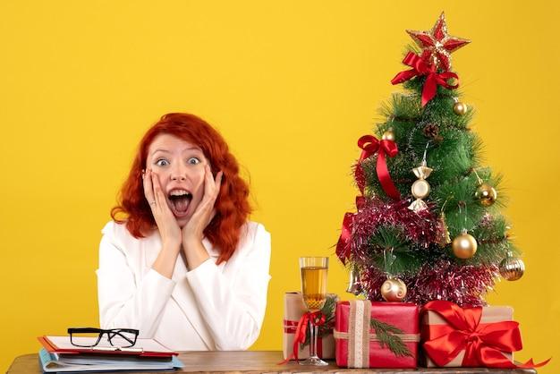 Medico femminile di vista frontale che si siede dietro la sua tavola con i regali di natale e l'albero su fondo giallo