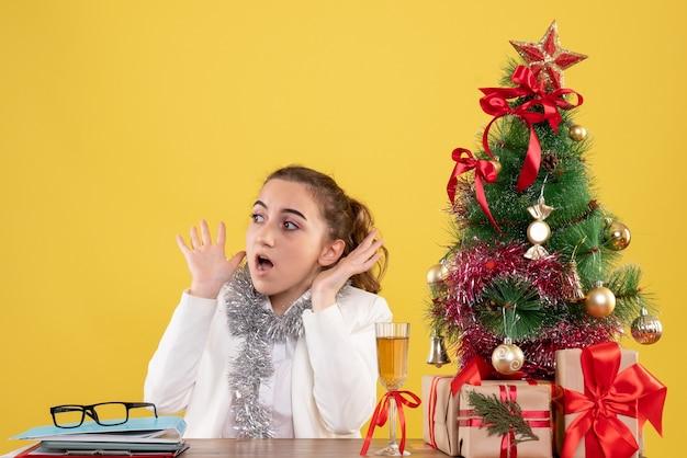 Medico femminile vista frontale seduto dietro il suo tavolo con la faccia spaventata su sfondo giallo con albero di natale e scatole regalo