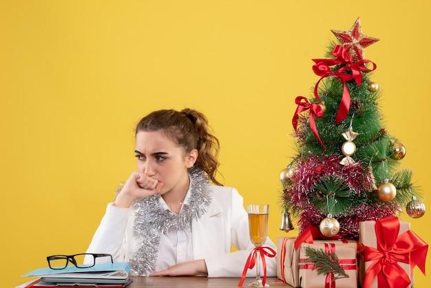 Medico femminile di vista frontale che si siede dietro il suo tavolo con il viso stressato su sfondo giallo con albero di natale e scatole regalo