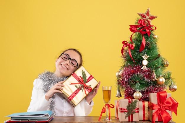 Medico femminile di vista frontale che si siede dietro il suo tavolo con regali di natale e albero su sfondo giallo