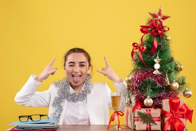 Medico femminile di vista frontale che si siede dietro il suo tavolo su uno sfondo giallo con albero di natale e confezioni regalo