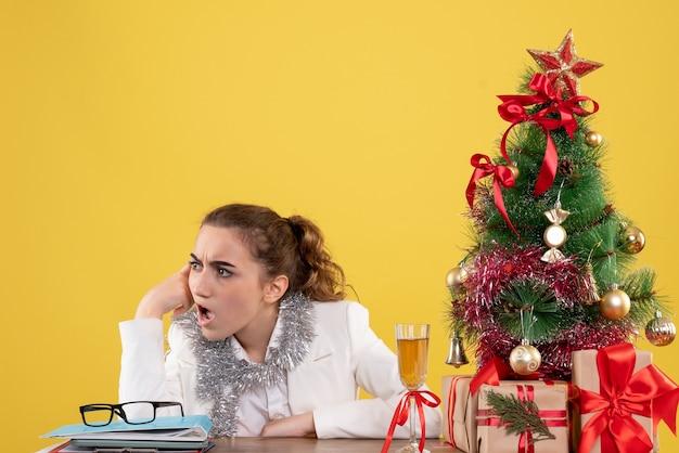 Medico femminile di vista frontale che si siede dietro il suo tavolo su sfondo giallo