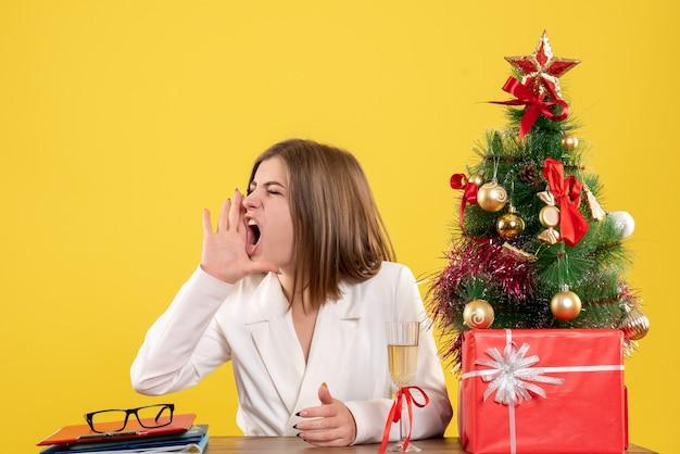 彼女のテーブルの前に座ってクリスマスツリーとギフトボックスと黄色の背景を呼び出す正面図の女性医師