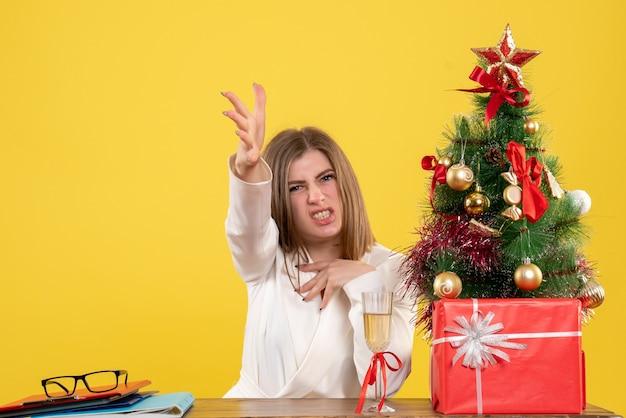 크리스마스 트리와 선물 상자와 노란색 배경에 불쾌한 그녀의 테이블 앞에 앉아 전면보기 여성 의사