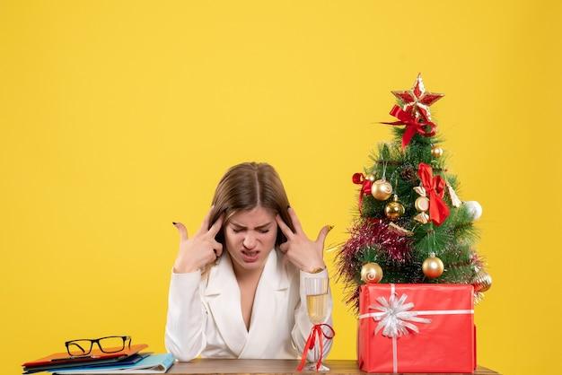 彼女のテーブルの前に座っている正面図の女性医師は、クリスマスツリーとギフトボックスと黄色の背景に疲れを感じています