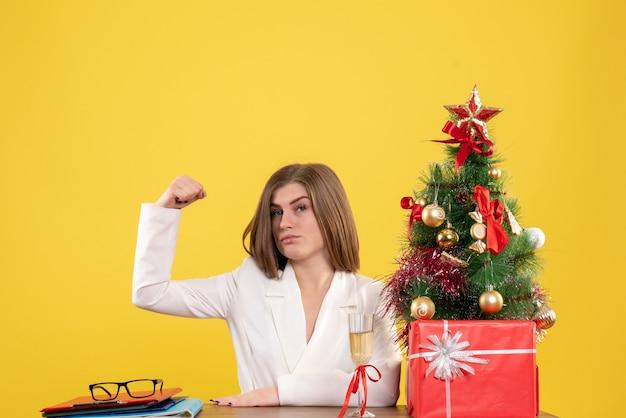크리스마스 트리와 선물 상자와 노란색 배경에 flexing 그녀의 테이블 앞에 앉아 전면보기 여성 의사
