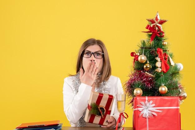 크리스마스 트리와 선물 상자와 노란색 배경에 선물을 들고 그녀의 테이블 앞에 앉아 전면보기 여성 의사