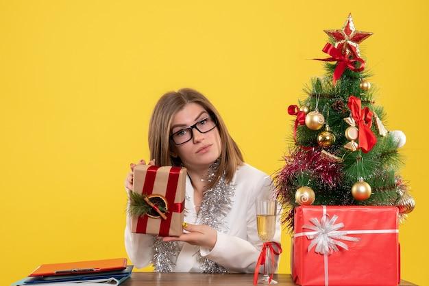 Вид спереди женщина-врач, сидящая перед своим столом, держа подарок на желтом фоне с рождественской елкой и подарочными коробками