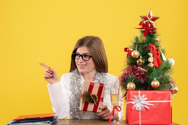 クリスマスツリーとギフトボックスと黄色の机の上にプレゼントを保持している彼女のテーブルの前に座っている正面図の女性医師