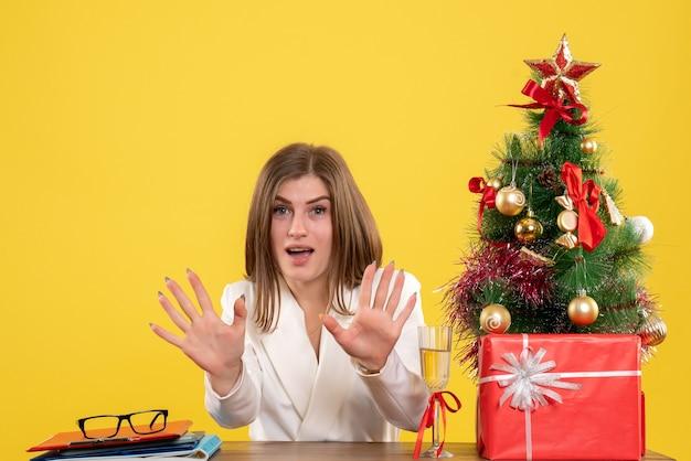 노란색 배경 크리스마스 새해 감정 병원 사무실 건강에 그녀의 테이블 앞에 앉아 전면보기 여성 의사