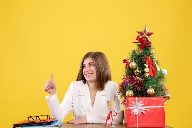 Вид спереди женщина-врач, сидящая перед своим столом на желтом фоне с елкой и подарочными коробками