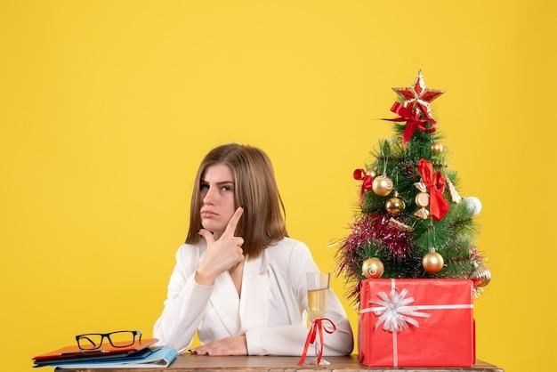 クリスマスツリーとギフトボックスと黄色の背景に彼女のテーブルの前に座っている正面図の女性医師