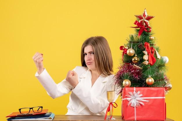 クリスマスツリーとギフトボックスと黄色の机の上の彼女のテーブルの前に座っている正面図の女性医師