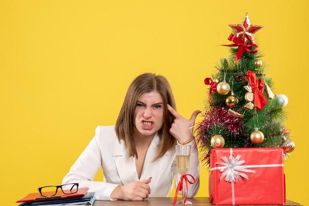 크리스마스 트리와 선물 상자와 노란색 바닥에 그녀의 테이블 앞에 앉아 전면보기 여성 의사