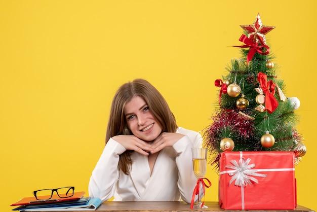 노란색 배경에 웃는 그녀의 테이블 앞에 앉아 전면보기 여성 의사