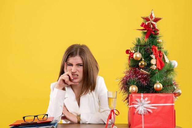 彼女のテーブルの前に座っている正面図の女性医師は、クリスマスツリーとギフトボックスで黄色の背景を強調