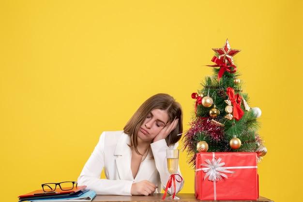 クリスマスツリーとギフトボックスと黄色の背景に疲れた彼女のテーブルの前に座っている正面図の女性医師