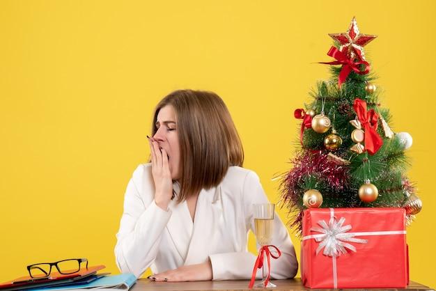 クリスマスツリーとギフトボックスと黄色の背景にあくびをする彼女のテーブルの前に座っている正面図の女性医師
