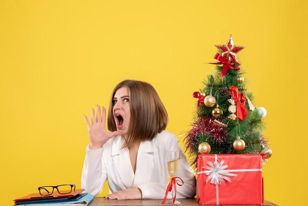 Вид спереди женщина-врач сидит перед столом на желтом фоне с елкой и подарочными коробками