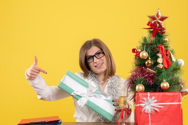 노란색 배경에 선물 및 나무와 테이블 앞에 앉아 전면보기 여성 의사