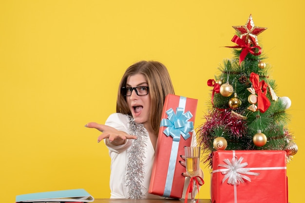 크리스마스 트리 및 선물 상자와 노란색 배경에 선물 및 트리 테이블 앞에 앉아 전면보기 여성 의사