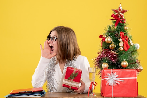 クリスマスツリーとギフトボックスと黄色の背景にプレゼントと木とテーブルの前に座っている正面図の女性医師