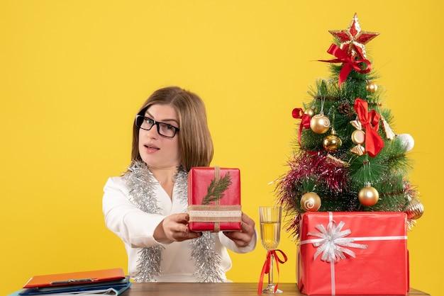 Вид спереди женщина-врач, сидящая перед столом с подарками и елкой на желтом фоне с рождественской елкой и подарочными коробками