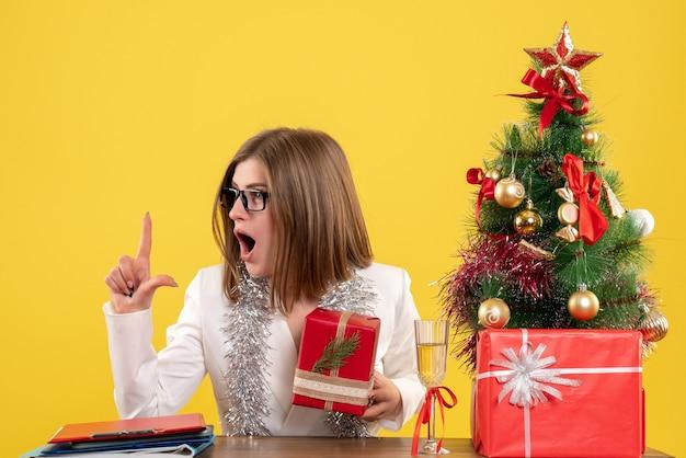 크리스마스 트리와 선물 상자와 노란색 책상에 선물과 나무와 테이블 앞에 앉아 전면보기 여성 의사