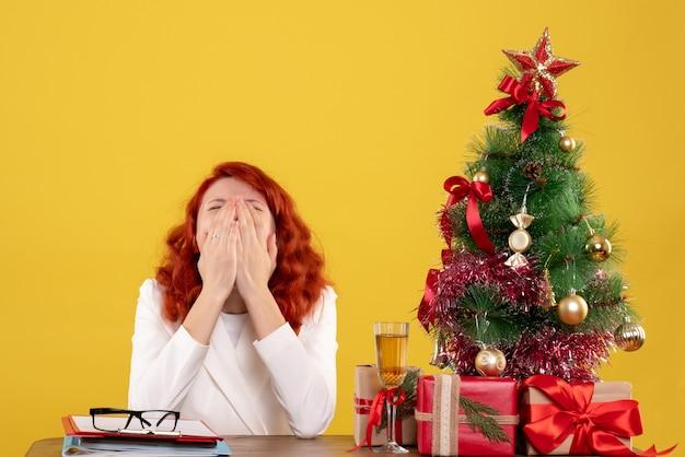 黄色の背景にプレゼントとクリスマスツリーあくびをしながらテーブルの前に座っている正面図の女性医師