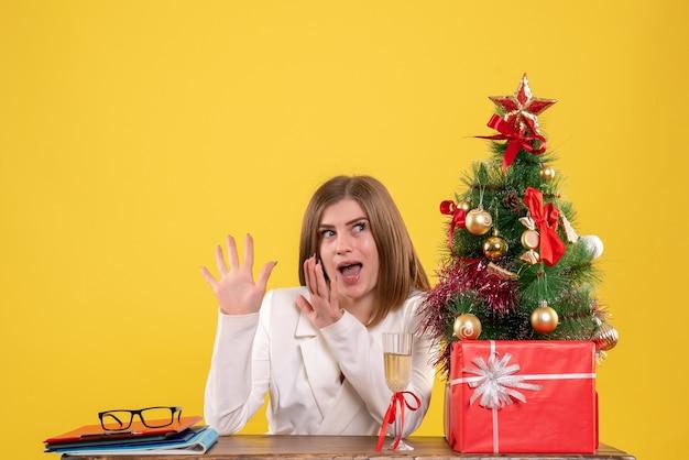 黄色の背景にクリスマスプレゼントと木とテーブルの前に座っている正面図女性医師