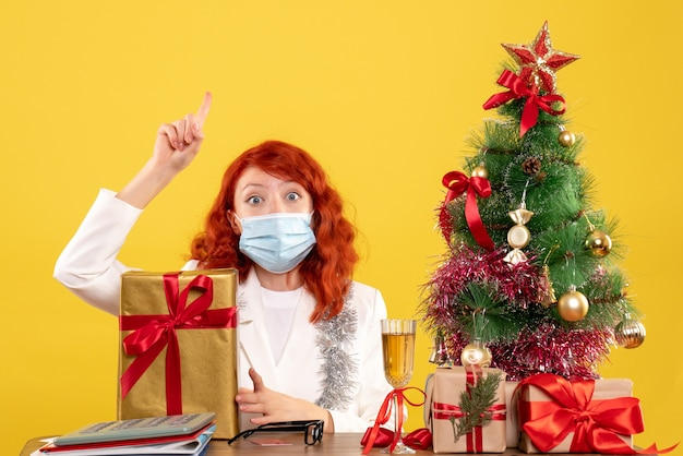 Вид спереди женщина-врач сидит в маске с рождественскими подарками и деревом на желтом фоне