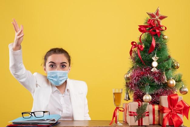 Вид спереди женщина-врач, сидящая в защитной маске, спорит на желтом фоне с елкой и подарочными коробками
