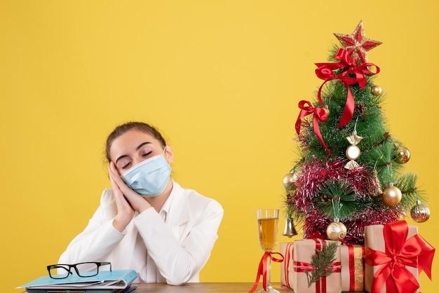 크리스마스 트리와 선물 상자와 노란색 배경에 피곤 느낌 보호 마스크에 앉아 전면보기 여성 의사