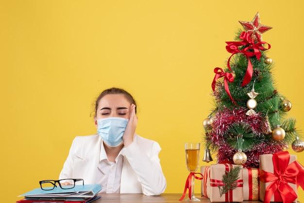 Вид спереди женщина-врач сидит в защитной маске на желтом фоне с елкой и подарочными коробками