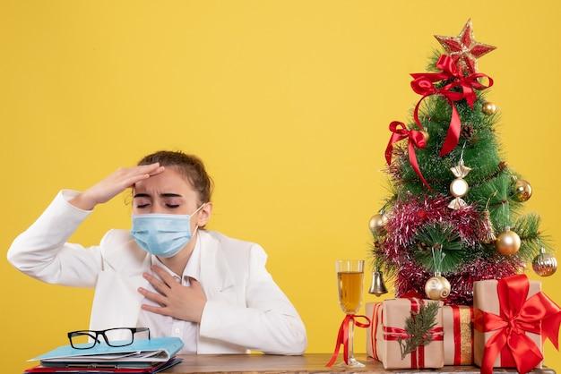 크리스마스 트리와 선물 상자와 노란색 배경에 보호 마스크에 앉아 전면보기 여성 의사