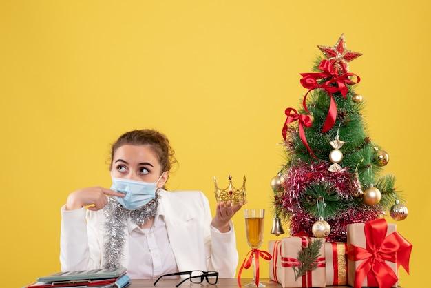 クリスマスツリーとギフトボックスと黄色の背景に王冠を保持している無菌マスクに座っている正面図の女性医師