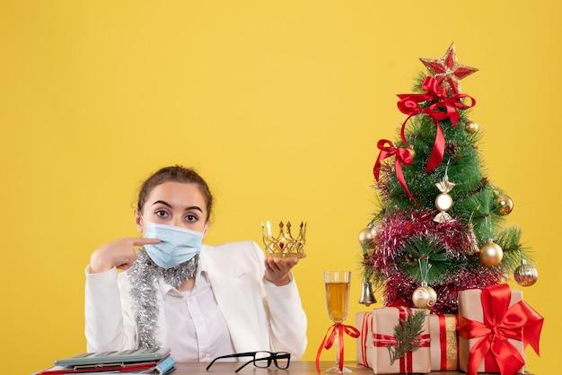 Вид спереди женщина-врач сидит в стерильной маске с короной на желтом фоне с елкой и подарочными коробками