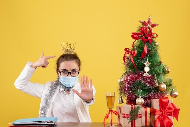 Вид спереди женщина-врач, сидящая в стерильной маске на желтом фоне с елкой и подарочными коробками