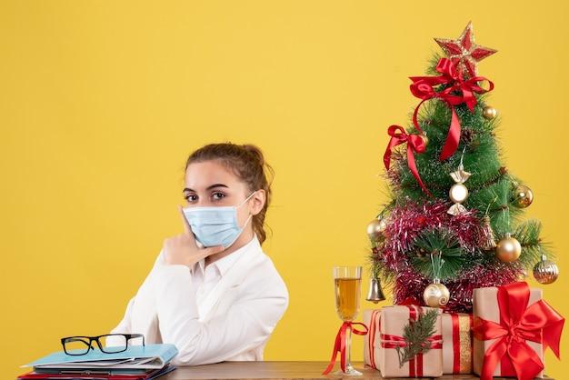クリスマスツリーとギフトボックスと黄色の背景に滅菌マスクに座っている正面図の女性医師