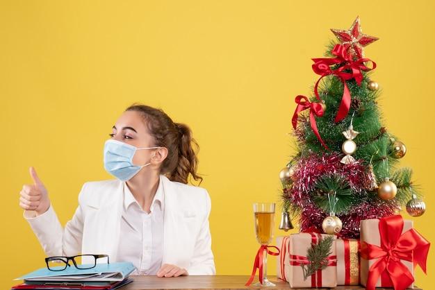 노란색 배경에 멸균 마스크에 앉아 전면보기 여성 의사