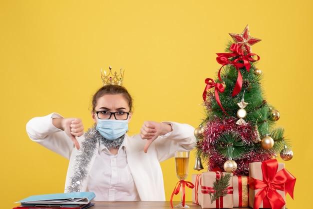 Вид спереди женщина-врач, сидящая в стерильной маске на желтом столе с елкой и подарочными коробками