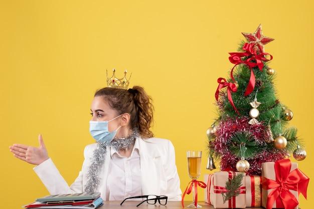 크리스마스 트리와 선물 상자와 노란색 배경에 악수하는 멸균 마스크에 앉아 전면보기 여성 의사