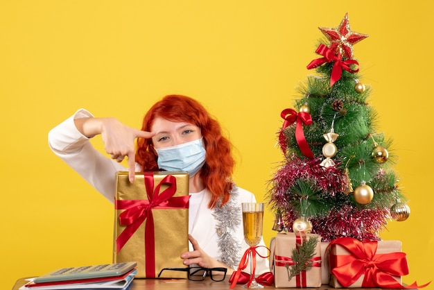 Front view female doctor sitting in mask with xmas presents and tree on yellow background with christmas tree and gift boxes