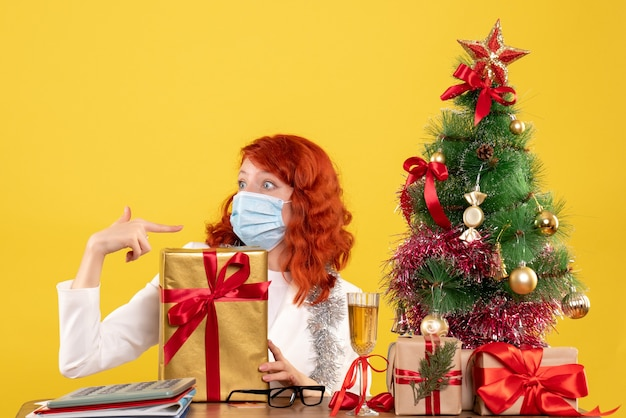 Front view female doctor sitting in mask with xmas presents and tree on yellow background