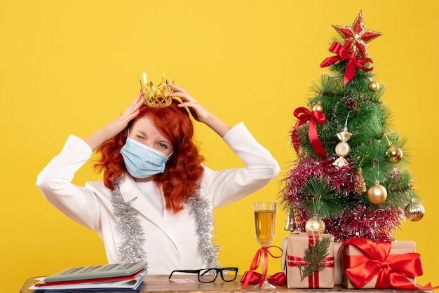 Front view female doctor sitting in mask with xmas presents wearing crown on a yellow background