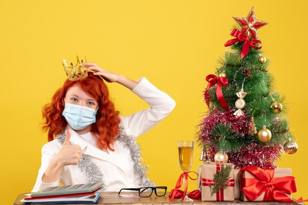Front view female doctor sitting in mask with xmas presents wearing crown on the yellow background