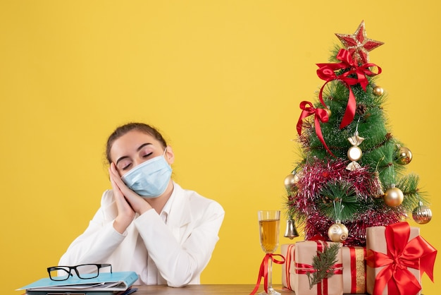 Medico femminile di vista frontale che si siede nella mascherina protettiva che si sente stanco su fondo giallo con l'albero di natale e le confezioni regalo